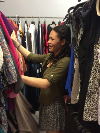 woman looks through second-hand clothes
