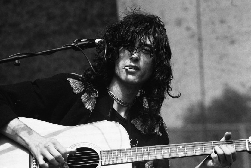Jimmy Page, cigarette in mouth as he strums his guitar (1978). Photo taken by Susan Ackeridge (under CC BY 2.0, no changes have been made.)