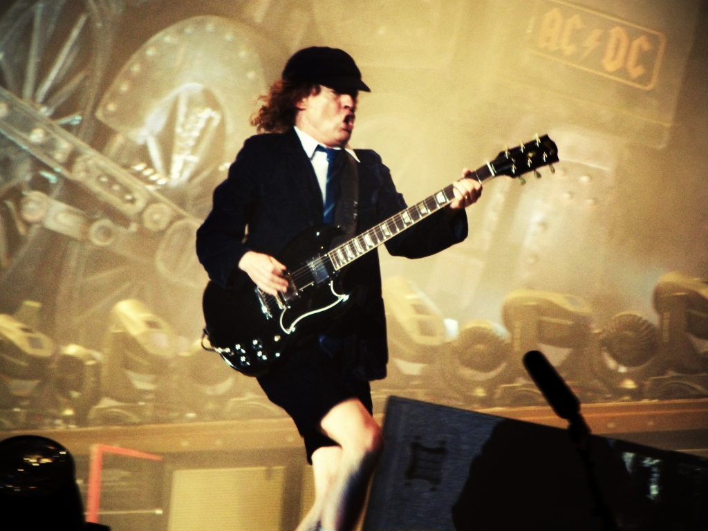 Angus Young, duck walking across stage during the Black Ice World Tour in Barcelona, Spain (2009). Photo taken by Ed Vill (under CC BY 2.0, no changes have been made.)