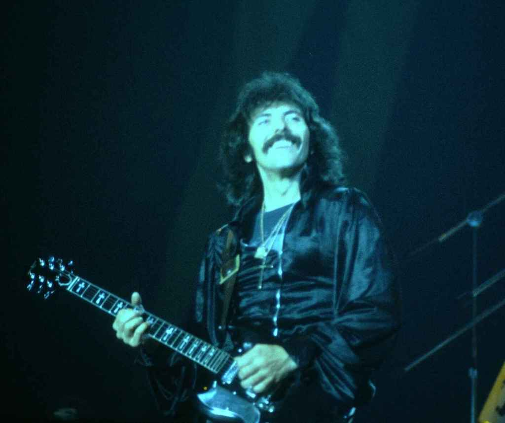 Tony Iommi, grinning on stage as he plays in the New Haven Coliseum (1978). Photo taken by Carl Lender (under CC BY 2.0, no changes have been made.)
